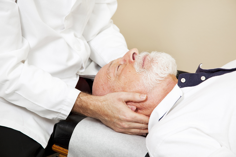 male patient laying down and receiving chiropractic treatment for his neck pain