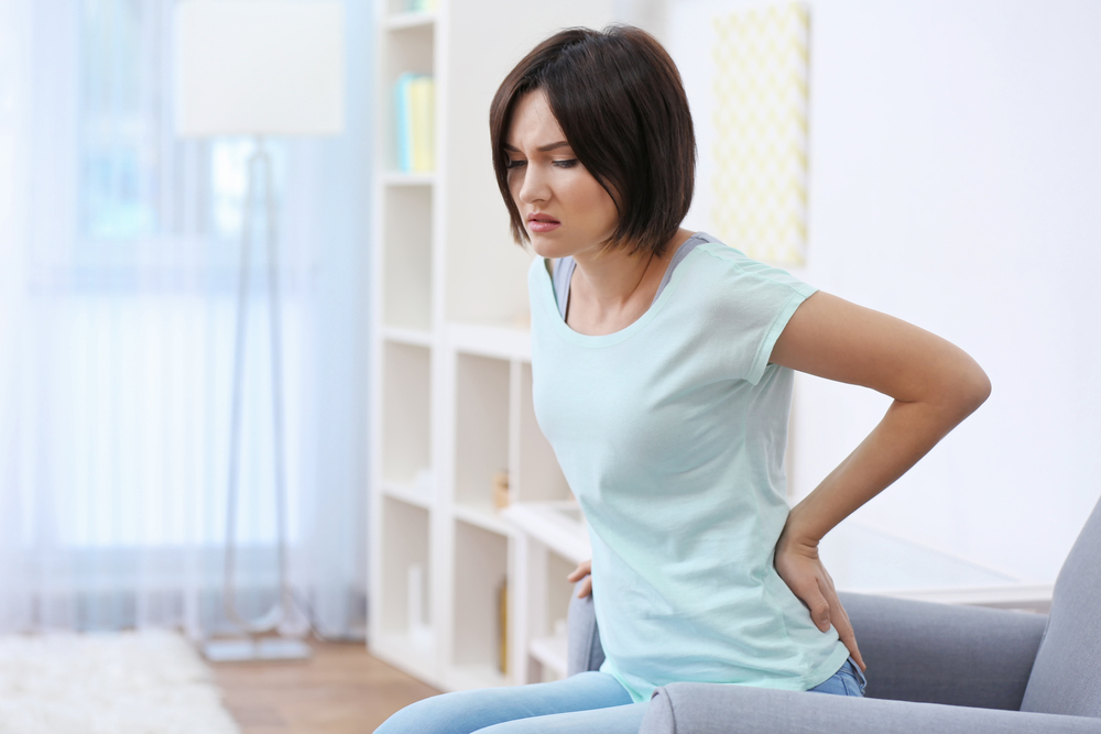 woman sitting on couch holding her back who needs chiropractic treatment for back pain