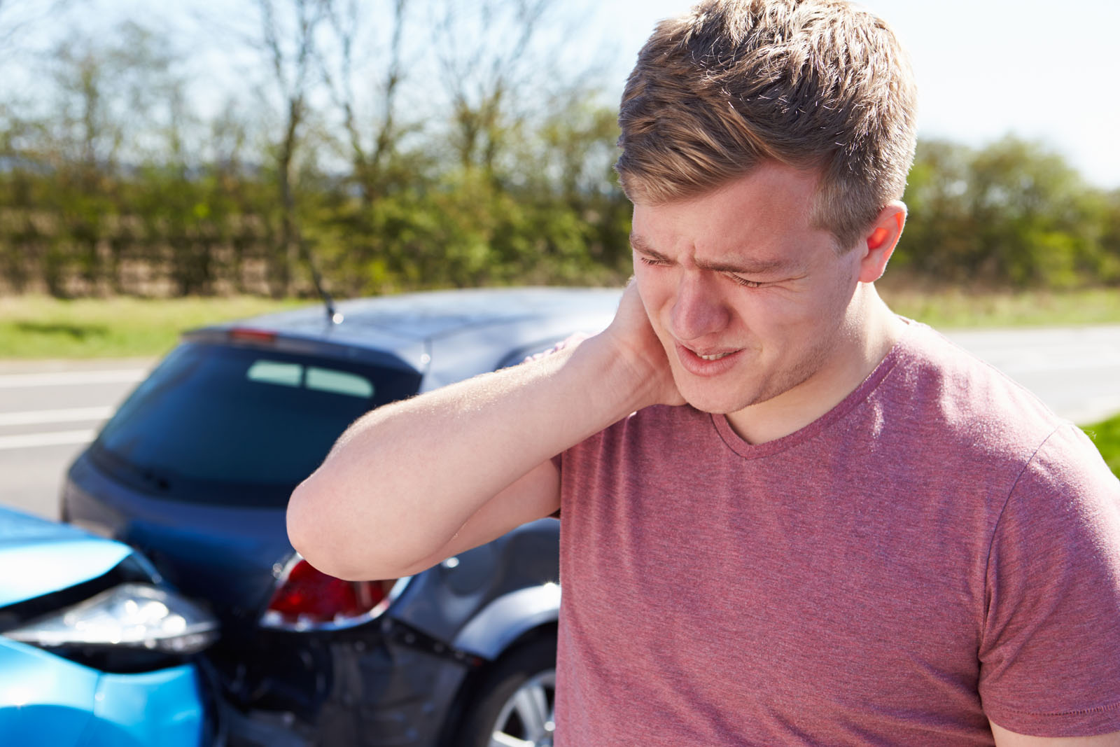 man holding his neck from whiplash pain from an auto accident injury; car accident in the background